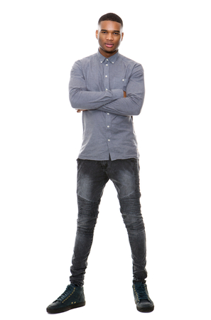 Full length portrait of a young african american man standing with arms crossed on isolated white background