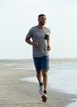 african american male: Young black man running on beach to keep fit