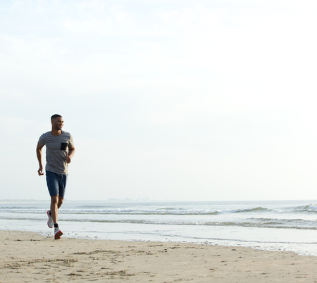 african american male: Young fit african american man running at the beach. Healthy lifestyle
