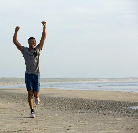 Young black man running on beach with arms raised up in celebration