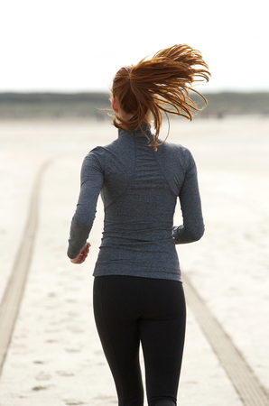 woman from behind: Rear view young woman running alone at the beach