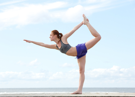 Young woman balancing on one leg in yoga stretch position at the beach photo