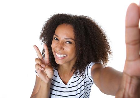 simbolo de la paz: Close up retrato de una mujer joven feliz que muestra signo de la paz en Autofoto Foto de archivo