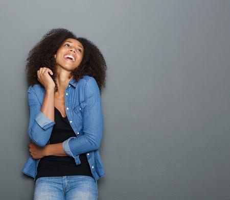 africanas: Retrato de una mujer de raza feliz joven africano riendo sobre fondo gris