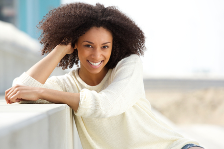 Close up portrait of a smiling african american woman with curly hair sitting outdoors 스톡 콘텐츠