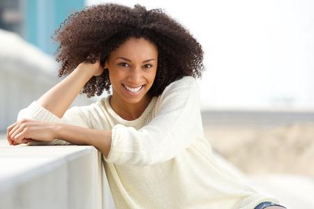 Close-up portret van een lachende African American vrouw met krullend haar in openlucht zitten
