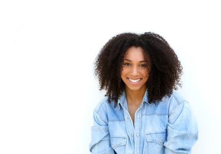 격리 된 흰색 배경에 웃 고 곱슬 머리와 매력적인 젊은 흑인 여성의 초상화를 닫습니다