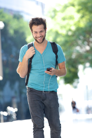 man in jeans: Portrait of a cheerful young man walking outdoors with bag and mobile phone