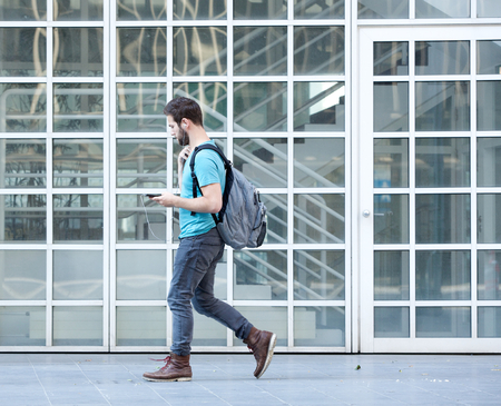 from side: Side view portrait of a male student walking on campus with bag and mobile phone