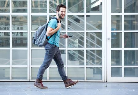 Vista lateral retrato de un hombre joven que camina en la acera con el teléfono móvil y el bolso
