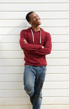 african american male: Portrait of a happy young black man standing against white background with arms crossed