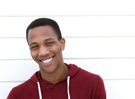 CLOSE UP FACE: Close up portrait of a handsome african american man smiling on white background