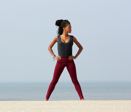 hands on hip: Portrait of a young black woman standing at beach with hand on hips