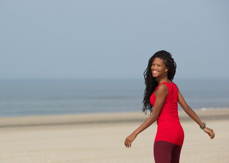 looking away: Portrait of a smiling african american woman walking at the beach