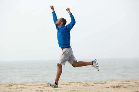 Young african american man running with hands raised at the beach photo