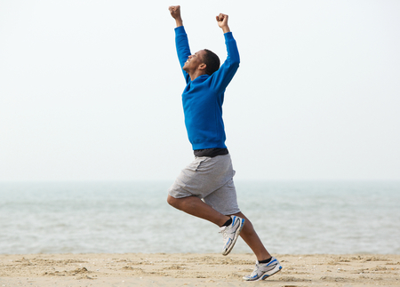 Young black man running at the beach with arms raised in victory
