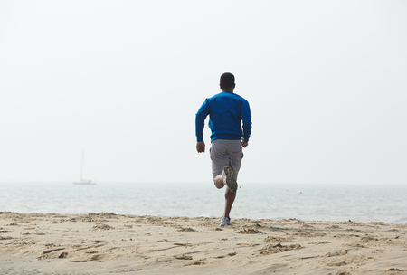 Rear view african american man running on the beach Stock Photo