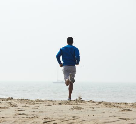 Achteraanzicht Afro-Amerikaanse man joggen op het strand Stockfoto - 32991149