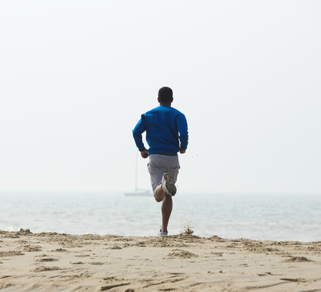 Rear view african american man jogging at the beach Stok Fotoğraf