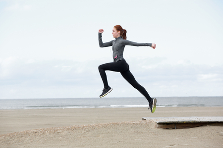Side view young female runner jumping outdoors photo