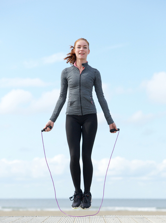 skip: Active young woman jumping with skipping rope outdoors