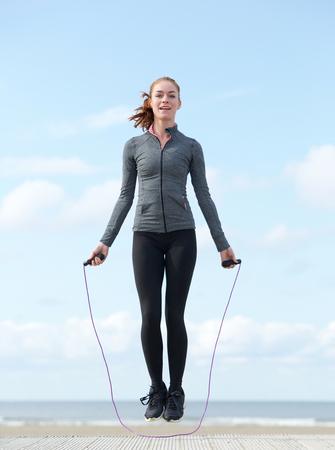 saltar la cuerda: Mujer joven activa que salta con la cuerda que salta al aire libre