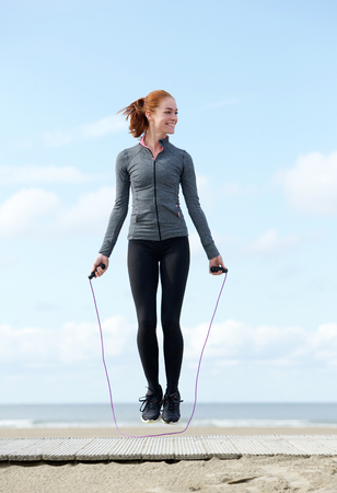 Young woman exercising with jump rope outdoors