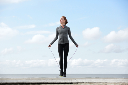 woman rope: Sporty woman warming up with jump rope outdoors
