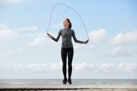 gente saltando: Mujer joven sana con cuerda de saltar en la playa