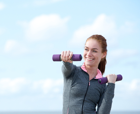 woman outdoor: Young woman exercising with aerobic weights outdoors
