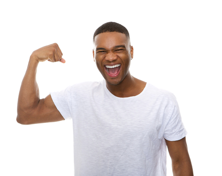Close up portrait of a happy african american man flexing arm muscle Stock Photo