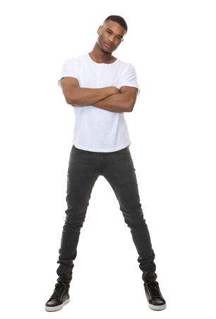 Full length portrait of a confident young man posing with arms crossed on isolated white background Stock Photo