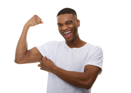 Close up portrait of a happy young man flexing bicep muscle photo