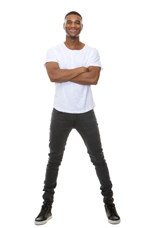 Full length portrait of a cool young guy smiling with arms crossed on isolated white background photo