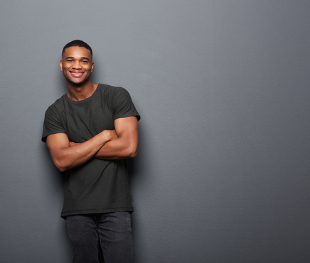 Portrait of a happy young man standing with arms crossed on gray background Imagens