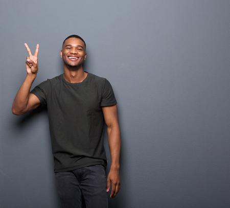 손 평화 기호를 보여주는 웃고있는 젊은 남자의 초상