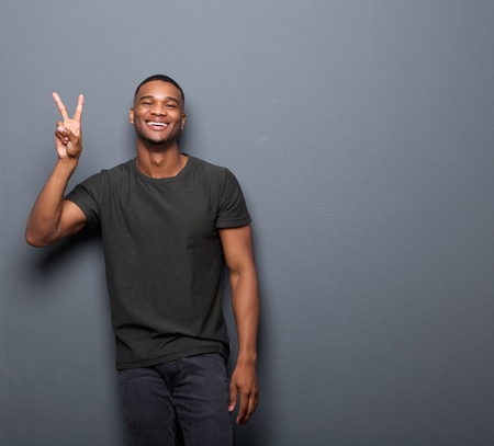 Portrait of a young man smiling showing hand peace sign Фото со стока