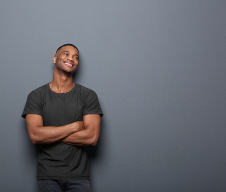 african fashion: Portrait of a cheerful young man smiling with arms crossed on gray background