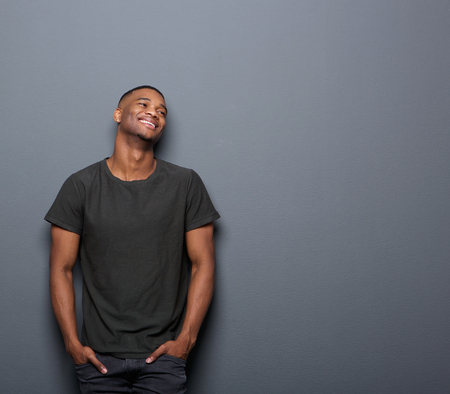 Portrait of a cheerful young man smiling in gray background Stock Photo