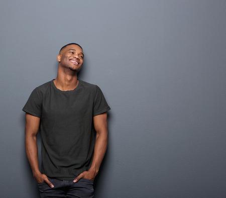 modelos negras: Retrato de un joven alegre sonriente en fondo gris