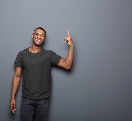 one finger: Portrait of a cool guy smiling and pointing finger on copy space gray background