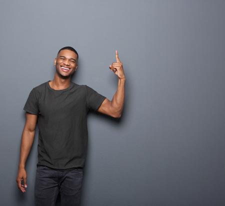 dedo �ndice: Retrato de un hombre fresco sonriendo y se�alando el dedo en copia espacio fondo gris