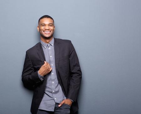 negras africanas: Retrato de un hombre afroamericano de moda sonriente sobre fondo gris Foto de archivo