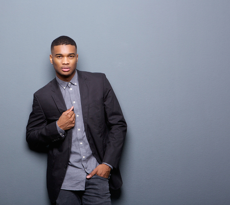 Portrait of a cool african american man with black business jacket posing on gray background