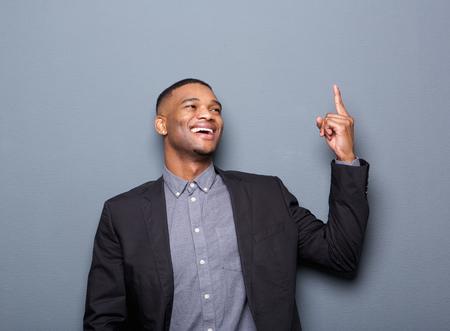 black business man: Portrait d'un homme d'affaires noir doigt heureuse pointant sur fond gris