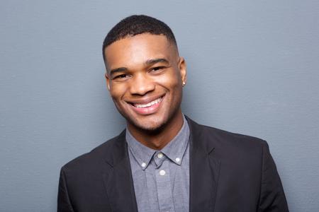 Close-up portret van een modieuze zwarte man glimlachend op grijze achtergrond Stockfoto
