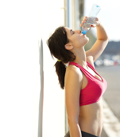 Beautiful sports woman drinking water from bottle\ outdoors