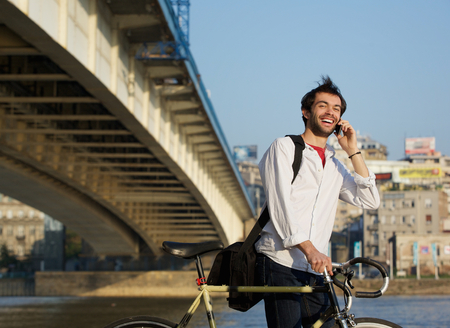 Portrait of a happy man walking outdoors with bike and mobile phone photo