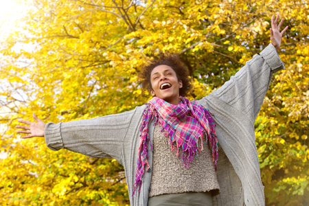 arms raised: Portrait of a carefree young african american woman with arms outstretched outdoors in autumn