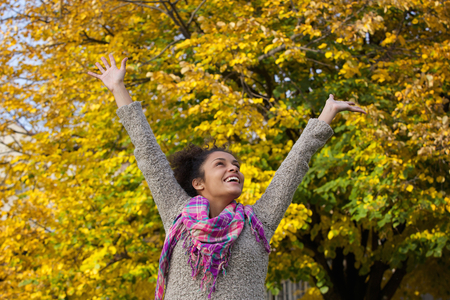 happy african woman: Portrait of a carefree young woman enjoying autumn with arms raised